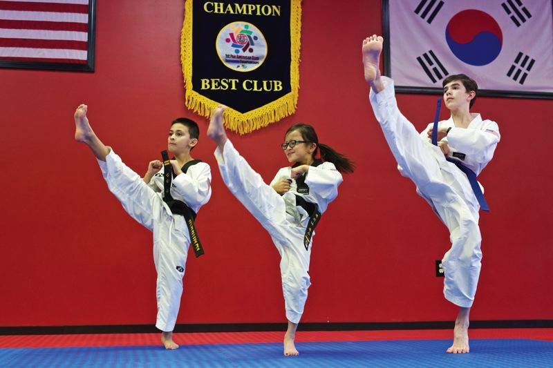 TIMES PHOTO: JAIME VALDEZ - Shawn Jones, 10, his sister, Zaina, 8, both from Tualatin and Cole Noretto, 12, who lives in Tigard, demonstrate how how to do a front-kick at the U.S. World Class Taekwondo at Sherwood Market Center. The three Taekwondo students will demonstrate their craft during a grand re-opening this Saturday.