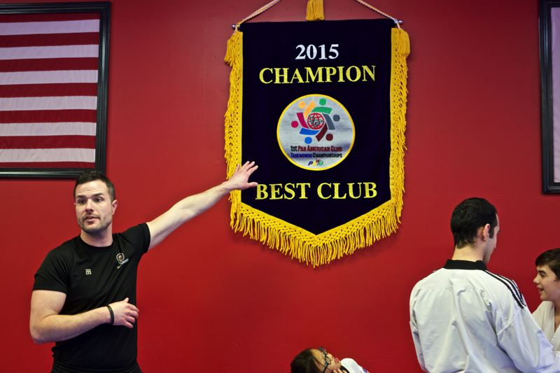 TIMES PHOTO: JAIME VALDEZ - Michael Tornincasa, owner and instructor at U.S. World Class Taekwondo, points to a banner that hangs on the wall of the Sherwood studio: Best Club at the 2015 Pan American Club Taekwondo Championships.