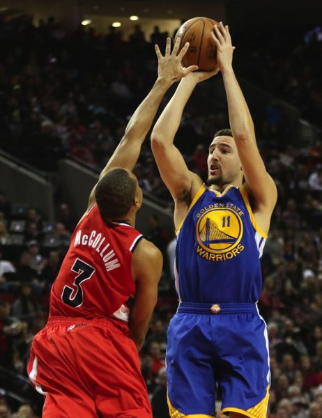 TRIBUNE PHOTO: JAIME VALDEZ - Klay Thompson (right) of the Golden State Warriors shoots over Trail Blazers guard CJ McCollum.