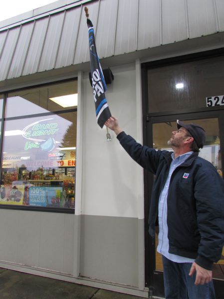 PAMPLIN MEDIA GROUP: COURTNEY VAUGHN - Greg Engstrom, co-owner of Engstrom Food Mart in Scappoose, places a Carolina Panthers flag above the entrance to the Chevron gas station and mini mart. The flag has been displayed at the gas station all week, despite an attempt from vandals to remove the flag.