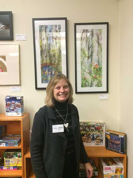 ESTACADA NEWS PHOTO: EMILY LINDSTRAND - Connie Athman stands with several of her entries in the Celebration of Watercolors show at the Estacada library.