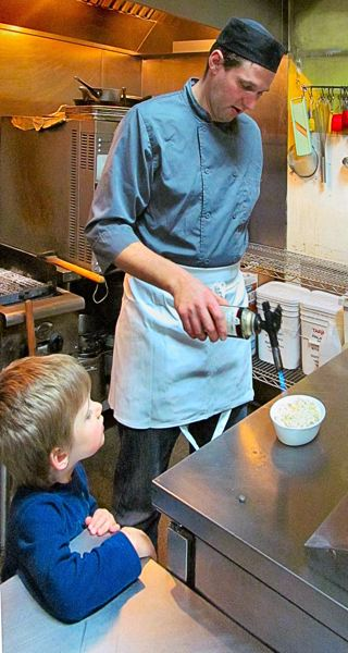 PHOTO BY DICK TRTEK - Joris Barbaray, co-owner of Mezza Restaurant in Woodstock, shows his son, Triatan, how to use a blowtorch to finish off a crème brulee.