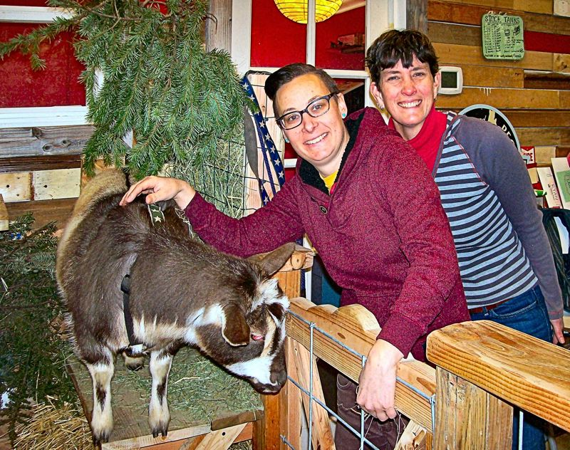 RITA A. LEONARD - One of Naomis pet goats, Binga, poses with her farm supply stores sales staff, Katie and Becca.