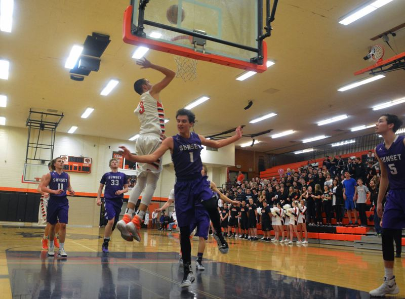 TIMES PHOTO: MATT SINGLEDECKER - Beaverton senior forward Niko Bevens puts up a layup over Sunsets Ely Kelton in the fourth quarter of the Beavers win over Sunset on Friday.
