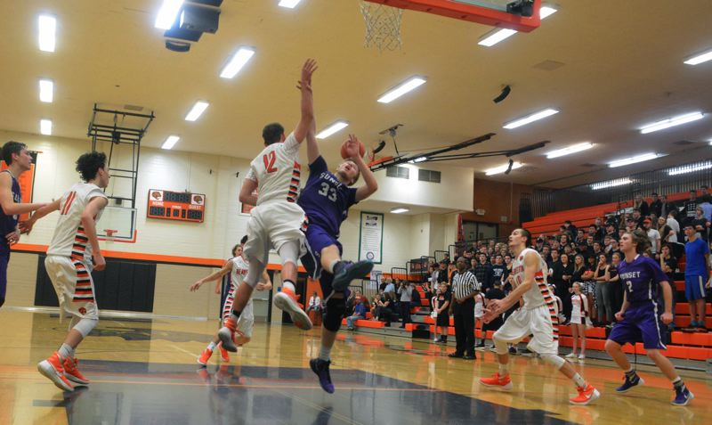 TIMES PHOTO: MATT SINGLEDECKER - Sunset junior power forward Reed Brown and Beaverton junior power forward Hunter Sweet battle for a rebound during the Beavers win over the Apollos on Friday.