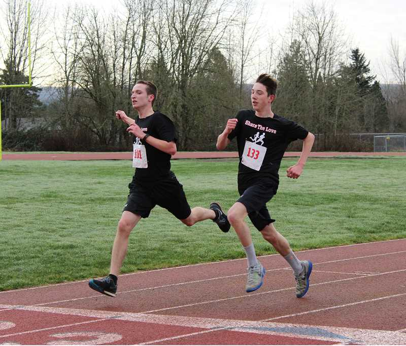 AUTUMN BARBER - Keenan Huffman and Daniel Morris cross the finish line. Huffman (101) came in second and Morris (133)  third in Molalla High Schools Share the Love 5K Red Run Saturday at Heckard Field in Molalla.