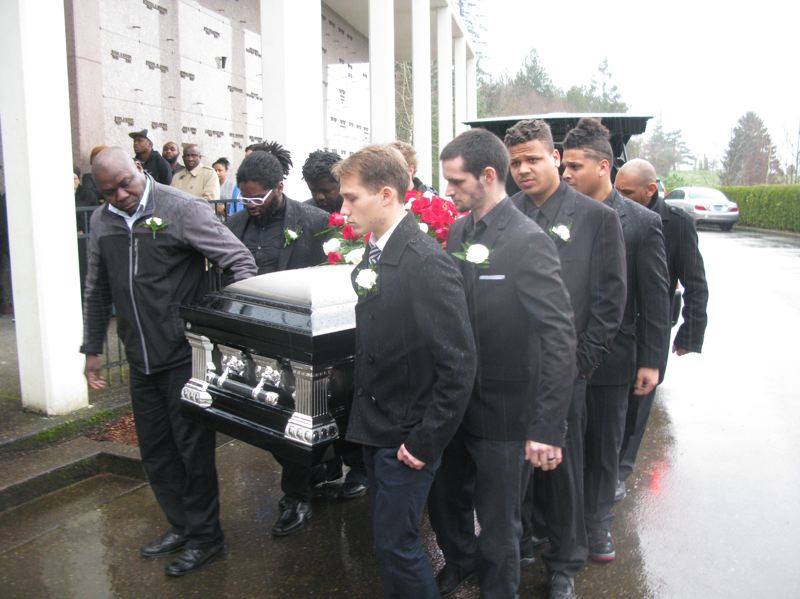 PHOTO BY RAYMOND RENDLEMAN - Pallbearers carry Christopher Kalonji's casket from the hearse to the funeral site.