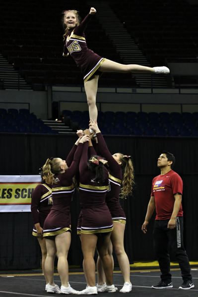 PHOTO BY BRIAN MONIHAN - Milwaukie High School cheerleaders show their skills in raising up an athlete above their heads in the category for small 5A teams.
