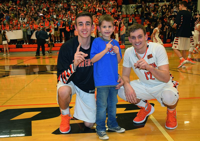 SUBMITTED PHOTO - Hillsboro's Elijah Maurer (center) hangs out with Beaverton varsity basketball players Drew Roper (left) and Hunter Sweet prior to the Beavers runaway win over Glencoe on Jam the Dam night at Beaverton High School on Friday.