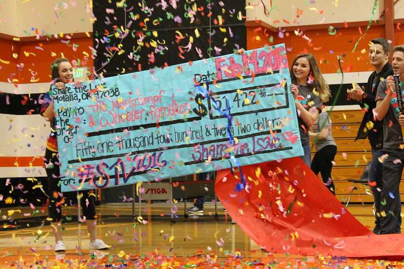 JIM BESEDA - MHS Senior Drew Vandenbroeder did the honors, pulling back the cover sheet to reveal a check for a record $51,422 during Friday's school assembly to cap the three week-long community Share the Love fundraiser to benefit the Karen Hartrampf family of Molalla and the Kristy Wheeler family of Colton.