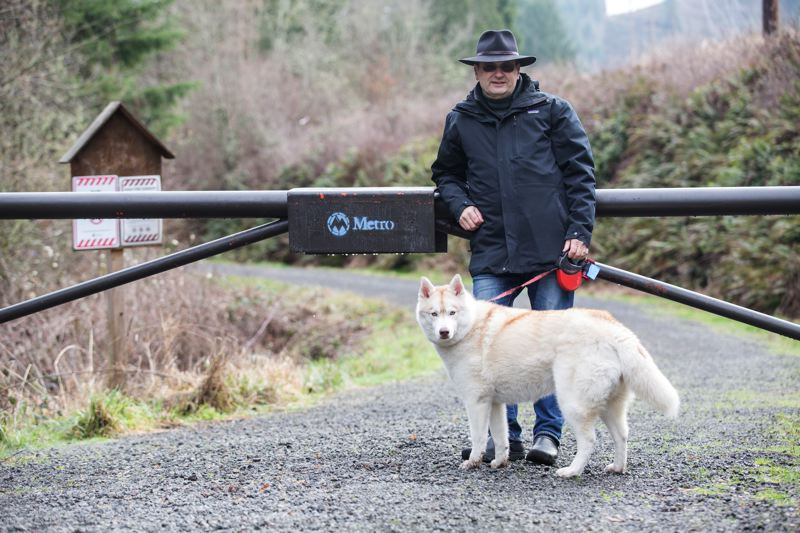 PAMPLIN MEDIA GROUP: JONATHAN HOUSE - PSU instructor and noted hiker Jim Thayer with his dog, Zoe, at a gate of where he can no longer walk her, due to Metros rules prohibition against dogs.