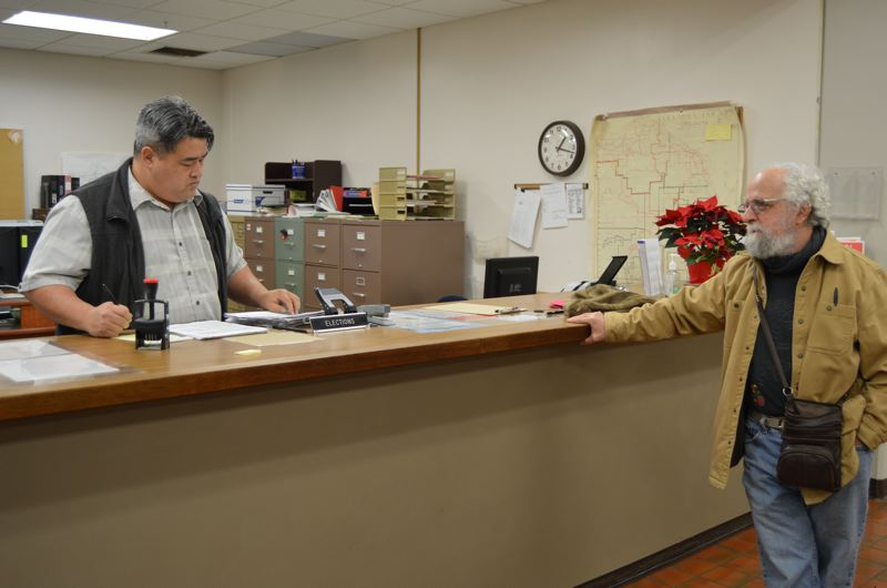 Dave Ehrenkranz, right, waits as Don Clack, Columbia County elections supervisor, reviews petition signatures submitted for a recall election against Columbia River PUD Director Craig Melton. The last of the mail-in ballots for the recall were turned in Tuesday evening.