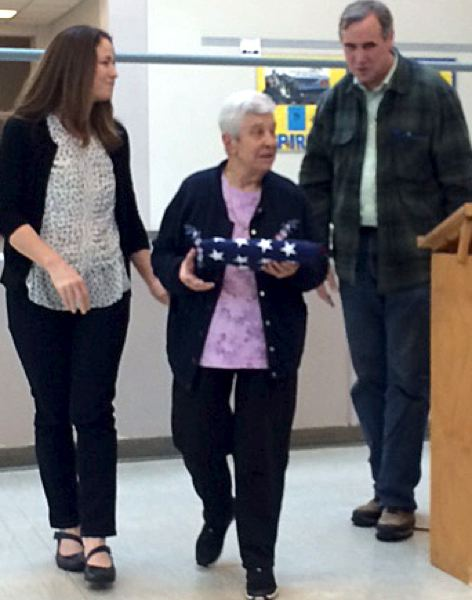 TRIBUNE PHOTO: PETER WONG - During a presentation on Saturday, Feb. 27, at Milwaukie High School, Anna Jones, co-founder of the Clackamas Service Center, gets a flag flown over U.S. Capitol from U.S. Sen. Jeff Merkley, as Executive Director Debra Mason looks on at left.