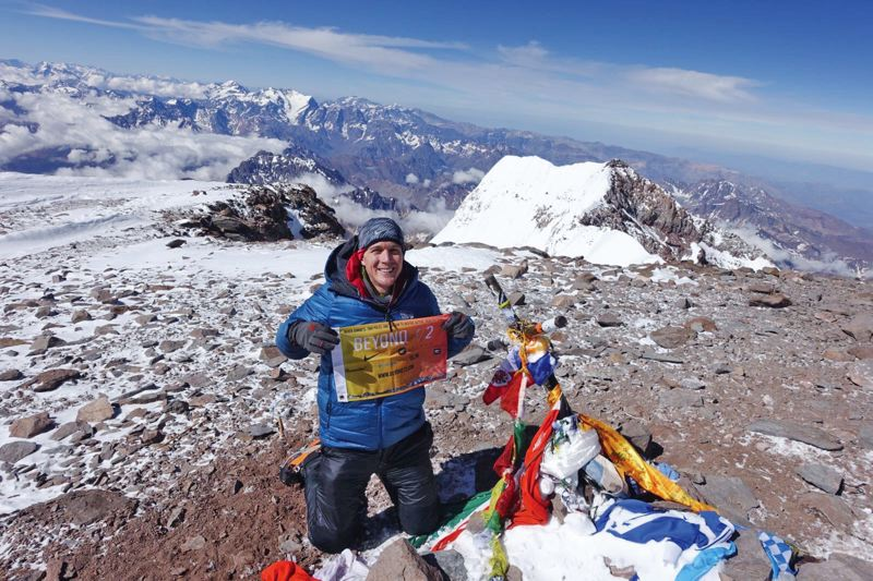 COURTESY PHOTOS: COLIN OBRADY - Portland resident Colin OBrady flashes a flag representing his nonprofit Beyond 7/2 at the summit of Aconcagua in Argentina. He decided to climb the 22,841-foot Aconcagua alone, and encountered strong winds.