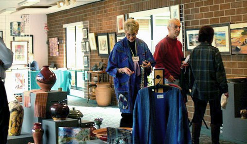 SUBMITTED PHOTO - Marilyn Adkins (left) strolls through a previous iteration of the Celebration of Creativity Fine Art Exhibit & Sale that opens on Thursday night at Southminster Presbyterian Church in Beaverton.