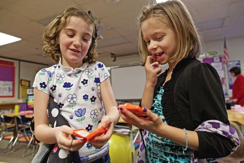 TIMES PHOTO: JAIME VALDEZ - Audrey Conrad and Sasha Tasker, second-graders in Lynne Martins class at Sexton Mountain Elementary School, look at how many steps theyve taken on their pedometers.