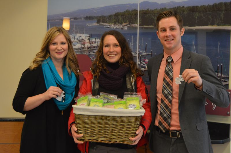 SPOTLIGHT PHOTO: NICOLE THILL - Victoria Worral (center), a Columbia City resident, and Cameron Willett (right), branch manager of the St. Helens Wauna Federal Credit Union, present a basket of 480 safety reflector key chains to Stephanie Wetherbee, an employee with the Oregon Department of Human Services, Wednesday, March 11. Wetherbee said the reflectors will be given to clients at the DHS Self Sufficiency office in St. Helens.