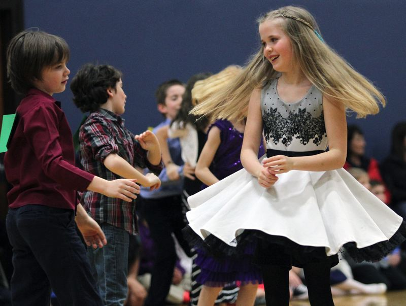TIMES PHOTO: MILES VANCE - Christopher Wittgow (left) and Maddy Moore, both fourth-graders at Mary Woodward Elementary School in Tigard, participate in the ballroom dancing showcase and friendly competition at Twality Middle School on Monday night.