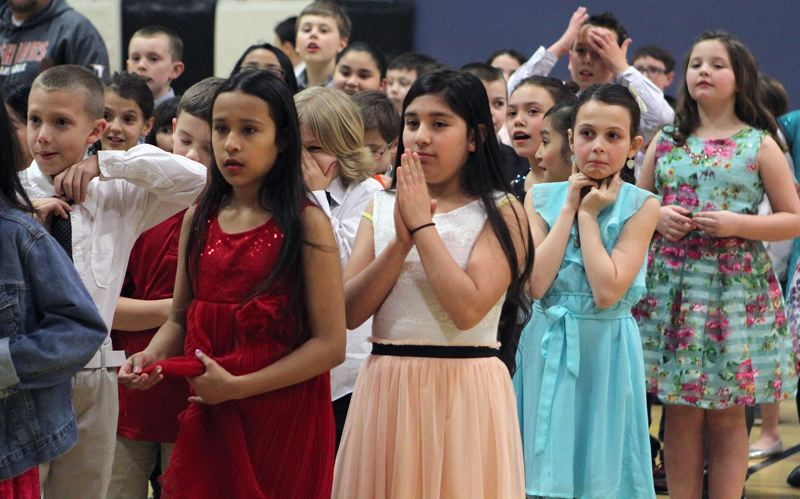 TIMES PHOTO: MILES VANCE - Yadira Donis Donis (red dress, left to right), Ashley Larios and Kiki Allen - all fourth-graders at Mary Woodward Elementary School in Tigard - prepare themselves for the ballroom dancing showcase and friendly competition at Twality Middle School on Monday night.
