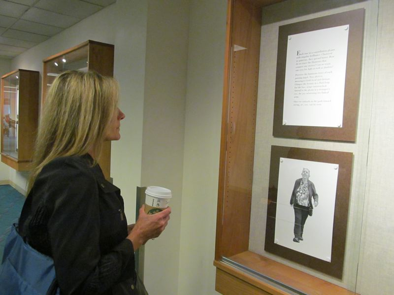 PHOTO BY DICK TRTEK - Deanne Horner, a Bend resident passing through Concourse A, reads Joanne Mulcahy's text in one of the display cases set up for 'Angels Passing.'