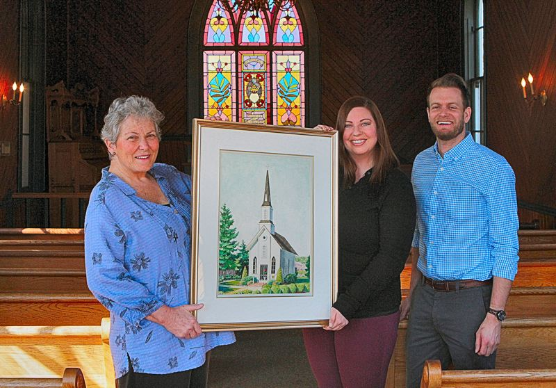 DAVID F. ASHTON - SMILE Board Member, and Chair of the Church Committee Nancy Walsh, left, accepts the original painting of the Oaks Pioneer Church from NGIC Director of Sales Jessie Hillman and Operations Manager Ian Vickrey.