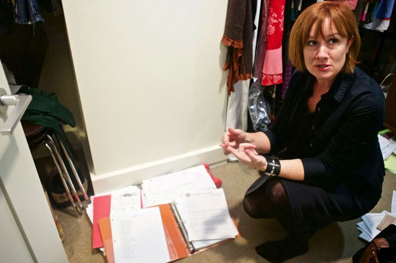 TRIBUNE PHOTO: JAIME VALDEZ - Portland Public Schools critic Kim Sordyl crouches in her closet to show the files of public documents she keeps on the district.