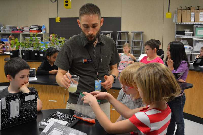 HILLSBORO TRIBUNE PHOTO: KATHY FULLER - Jay Well of Oregon State Universitys Bioenergy Education Initiative helps third graders Mason Wilson, Isabella Sarlo and Grace Garrison with a DNA extraction exercise.