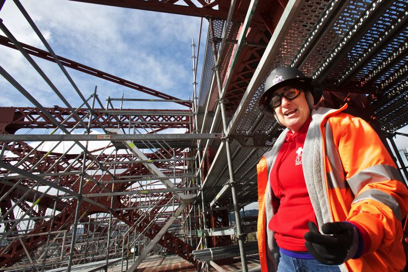 TIMES PHOTO: JAIME VALDEZ - Beaverton resident Michele Espinoza, an authorized Occupational Safety and Health Administration instructor, stands on scaffolding above the Broadway Bridge where she keeps the workers who are painting the bridge safe from injury.