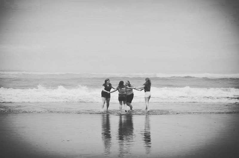 COURTESY PHOTO - Amie Cadd Musselwhite, Jessica Cadd, Stephanie Cadd (far right) and Samantha Cadd (back to camera) frolicked in the surf at Rockaway Beach in August 2013.