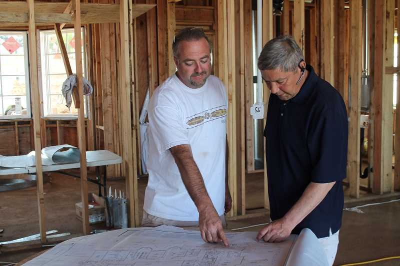 TIDINGS PHOTO: PATRICK MALEE - Gordon Root, left, looks over the blueprint for his home on the Street of Dreams property. Root previously developed a Street of Dreams at Remington Ridge in 1992, and has been heavily involved in the event since then.