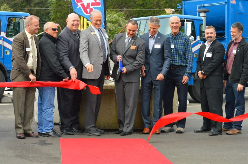 PMG PHOTO: JAKE BARTMAN - Cutting the ribbon at Republic Services' new fueling station in Wilsonville, from left: Clackamas County Commissioners Paul Savas and Jim Bernard, Clackamas County Commission Chair John Ludlow, Wilsonville Mayor Tim Knapp, Republic Services North County and Portland Metro Area General Manager Jason Jordan, Republic Services Area President Mike Huycke, Lake Oswego Mayor Kent Studebaker, Republic Services Area Director of Operations Bob Bennett and Lake Oswego City Councilor Jon Gustafson.
