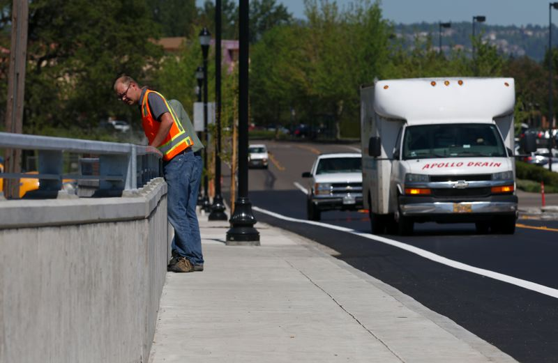 TIMES PHOTO: JONATHAN HOUSE - Project Manager Aaron Halling peers over the new Hocken Avenue bridge as it officially opened to traffic Tuesday afternoon.