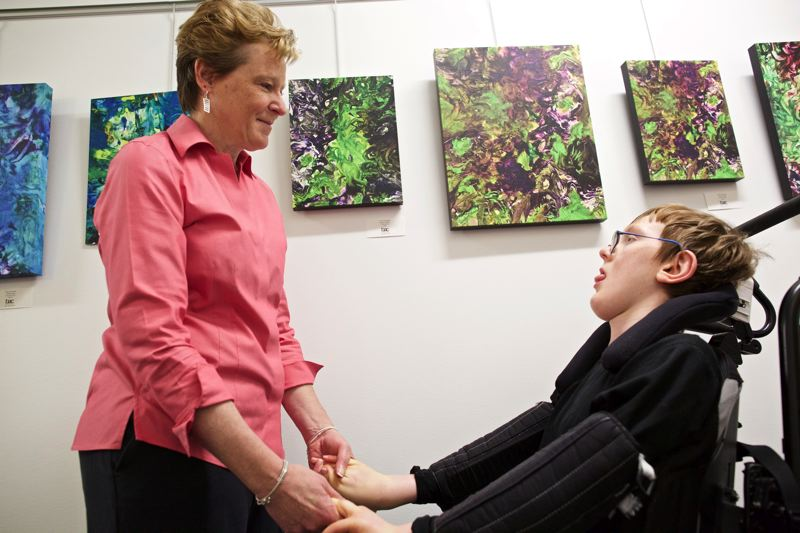 TIMES PHOTO: JAIME VALDEZ - Michelle Kennedy holds hands with Evan Kennedy, her 15-year-old son, on the fourth floor of the Beaverton Building. Evan Kennedy, who has an undiagnosed neuromuscular disorder, is showcasing his acrylic paintings this month at The Beaverton Building.