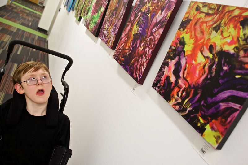 TIMES PHOTO: JAIME VALDEZ - Fifteen-year-old Evan Kennedy looks at his acrylic paintings being showcased on the fourth floor of The Beaverton Building.