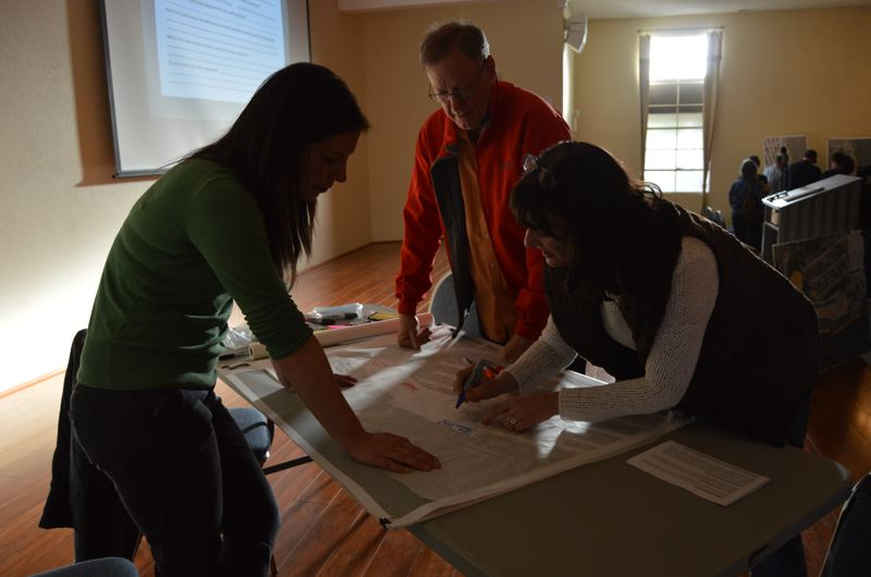 SPOTLIGHT PHOTO: NICOLE THILL - Lauren Wiritis, a consultant with Maul Foster Alongi, works with Herb Olson of St. Helens and Anjeanette Russell of Warren to sketch original ideas for the waterfront property. People were encouraged to draw on the map and give feedback at a table set up in the front of the room.