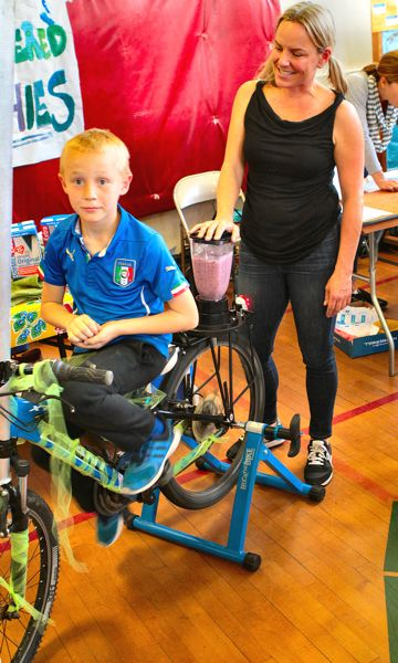 DAVID F. ASHTON - Duniway student Charlie supplies the pedal power, to help his mom - Wendy Foster - make smoothies in a bike-mounted blender.
