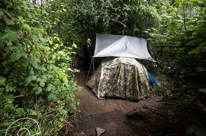TIMES PHOTO: JAIME VALDEZ - Police officer Brian Orth checks on a tent off of a Tigard trail. Orth, along with his partner Heather Wakem, consistently reach out to the homeless community to see whom they can help get off the street.