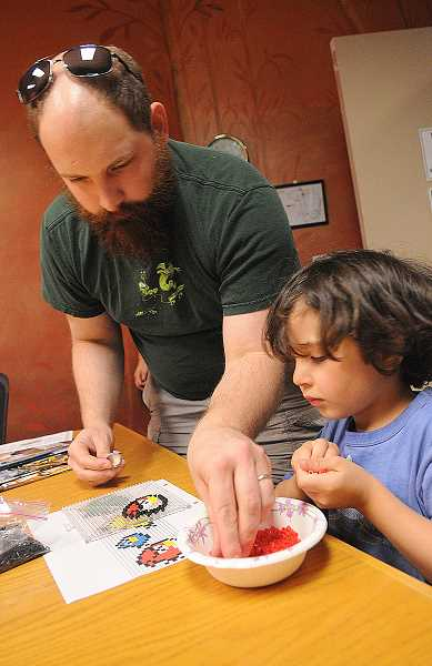 TIDINGS PHOTO: VERN UYETAKE - Justin Lowmaster and his son Owen work on an Angry Birds design using pearler beads.