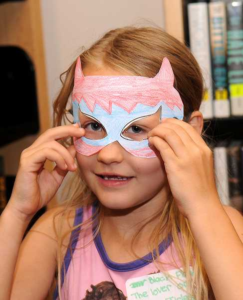 TIDINGS PHOTO: VERN UYETAKE - McKennah Whiting, 8, of West Linn designed her own superhero mask at Free Comic Book Day in West Linn.