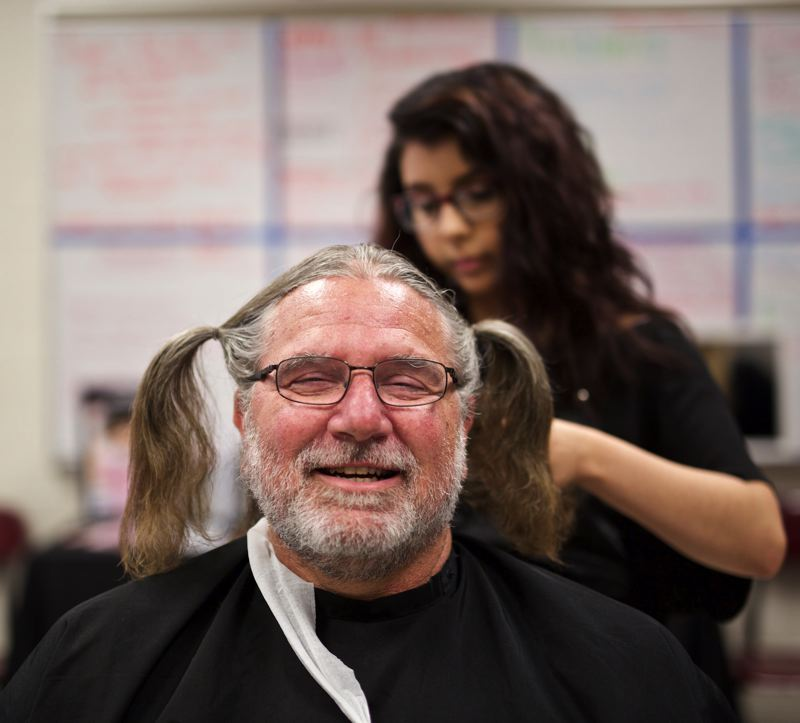 TIMES PHOTO: JAIME VALDEZ - Mark Trout, a special education teacher at Southridge High School, laughs while Collett Garza, a student at Paul Mitchell of Portland, puts his hair up in ponytails before having his hair cut for Locks from Hawks, a fundraiser for Locks of Love.