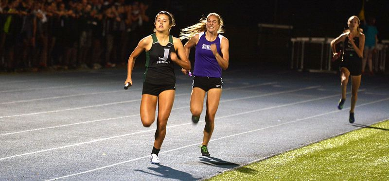 TIMES PHOTO: MATT SINGLEDECKER - Jesuit's Sydney Collins outruns Sunset's Nicole Griffiths to the tape during the final leg of the 4X400 relay at the Metro League district championship at Aloha High School.