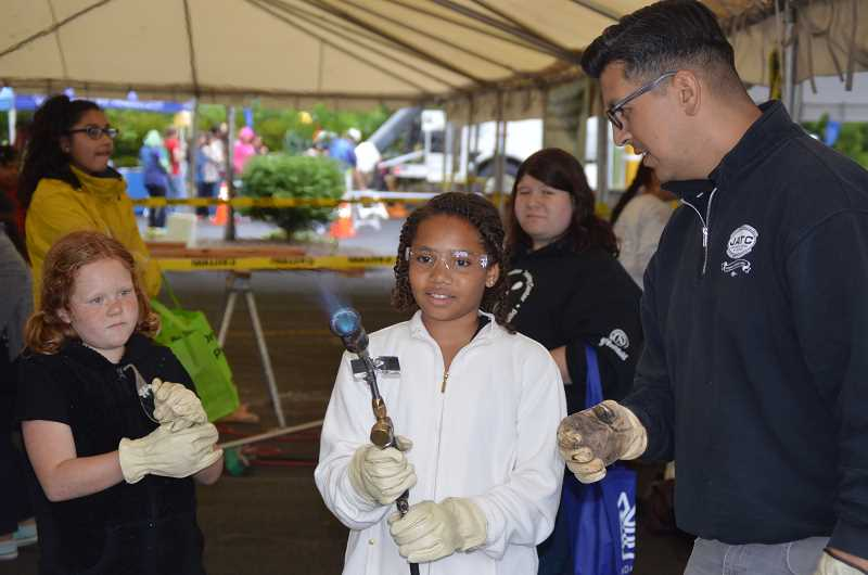 TRIBUNE PHOTO: COURTNEY VAUGHN - Olivia Fowlkes, 10, holds a torch used in roofing and weatherproofing, with the supervision of Joel Gonzalez, right, during a Women in Trades Career Fair held in Portland on Saturday. To her right, Autumn VanGorkum, 9, waits for her turn.