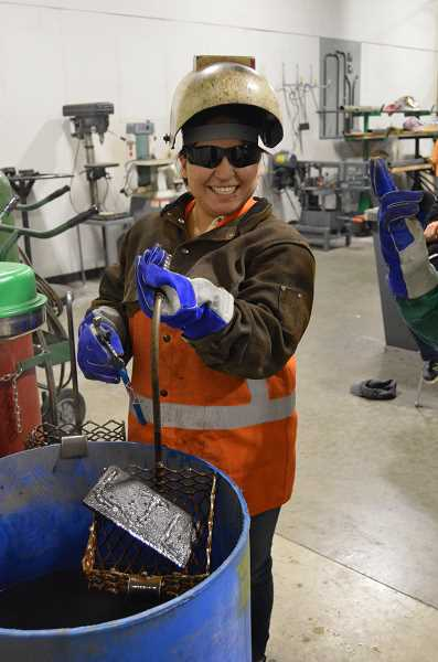 TRIBUNE PHOTO: COURTNEY VAUGHN - Irais Gandarilla submerges and sets one of the many welding projects made by students during the Women in Trades Career Fair. Gandarilla is an Oregon Tradeswomen, Inc. graduate and apprentice welder.