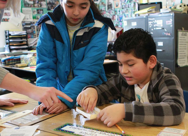 TIMES FILE PHOTO: MILES VANCE - Fifth-grade students Jacquelin Salcedo-Miranda and Carlos Torres-Hernandez build an air-powered miniature car during a STEM workshop at Tualatin Elementary School earlier this year.