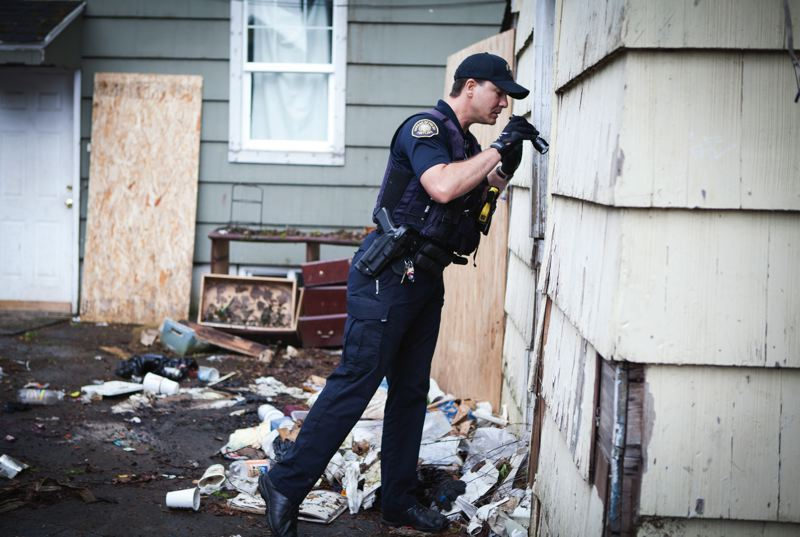 TRIBUNE PHOTO: ADAM WICKHAM - Portland police officer Rob Brown has been in this  abandoned house before and he's back - because it's clear that squatters have returned. Portland has over 400 abandoned homes but hasn't foreclosed on one  in more than 40 years.