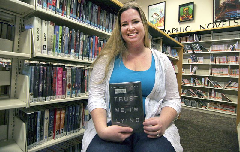 TIMES PHOTO: MILES VANCE - Beaverton author Mary Elizabeth Summer holds up one of the Beaverton City Library's copies of her first published book, 'Trust Me, I'm Lying.'