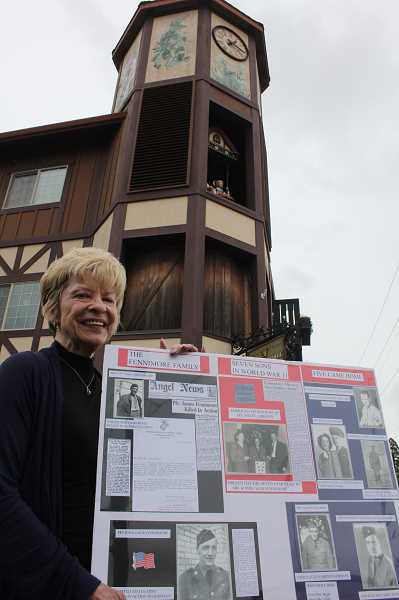 LINDSAY KEEFER - Henrietta Dill, developer of Edelweiss Village, which contains the Glockenspiel, is overseeing a $30,000 project that will temporarily replace the iconic clock-tower figures with military-themed ones. She is also encouraging residents to make posters honoring local veterans, like the one she's holding of the Fennimore family, which sent seven sons to war during World War II.