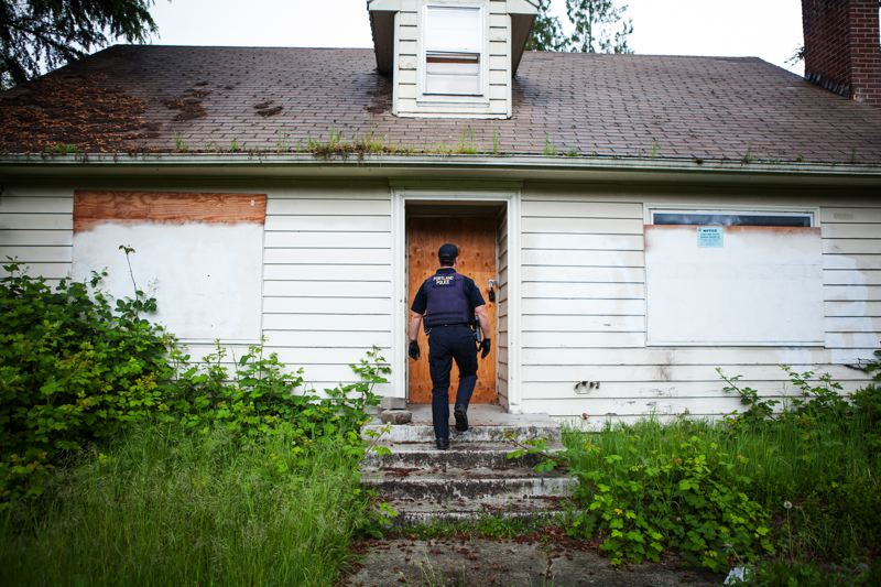 TRIBUNE PHOTO: ADAM WICKHAM - Portland police officer Joseph Young checks on a vacant eastside home. Police have a list of 430 abandoned eastside homes, but city foreclosure officials say they havent seen it.
