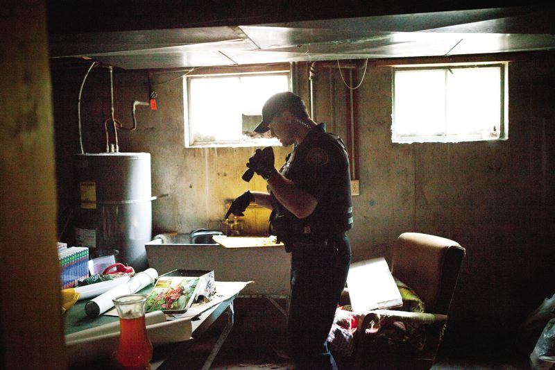 TRIBUNE PHOTO: ADAM WICKHAM - In the basement of another trashed abandoned home, Portland police officer Rob Brown finds bottles that squatters filled with urine, and a bucket where a fire had been lit.