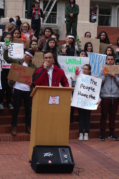 TRIBUNE PHOTO: JOSEPH GALLIVAN - PCC student Eddie Bolanos reads from a letter from United We Stand Oregon to the Forest Grove and surrounding school districts at a rally at Pioneer Courthouse Square May 22 2016, sparked by protests against a banner reading Build a Wall.